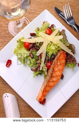 Grilled Salmon With Cheese And Vegetable Salad On White Plate