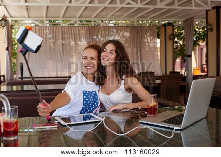 Girls making photo on cell telephone via self stick while relaxing in bar