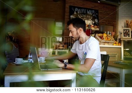Man owner of the organic shop making a monthly sales report on net-book while sitting at table