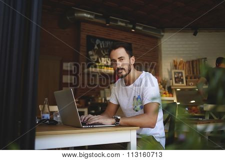Young man developer creating website on laptop computer while sitting in modern coffee shop interior
