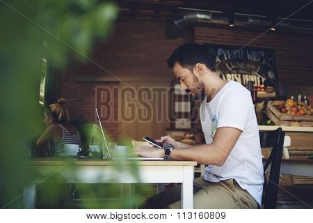 Handsome man reading text message during work on net-book in comfortable coffee shop