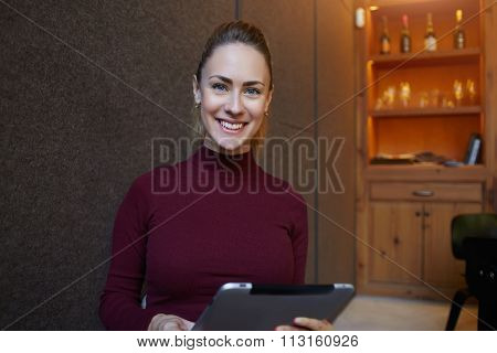 Half length portrait of a happy businesswoman holding touch pad while sitting in cozy restaurant
