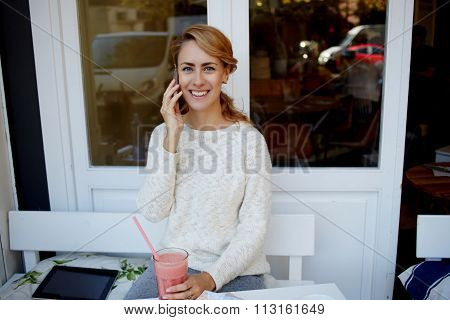 Happy woman having pleasant conversation on mobile phone during lunch break in modern coffee shop