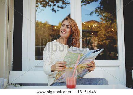 Smiling hipster girl dreaming about trip to Europe while resting in modern restaurant