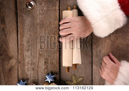 A list of Christmas wishes in Santa Claus hands on wooden background