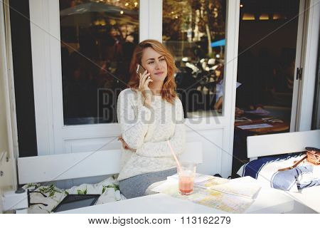 Beautiful young woman tourist calling on cell telephone while relaxing in modern coffee shop