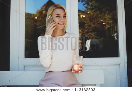 Cheerful female student talking on mobile phone while enjoying rest in cozy restaurant