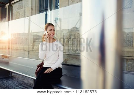 Happy hipster girl talking on cell telephone while sitting on station bench