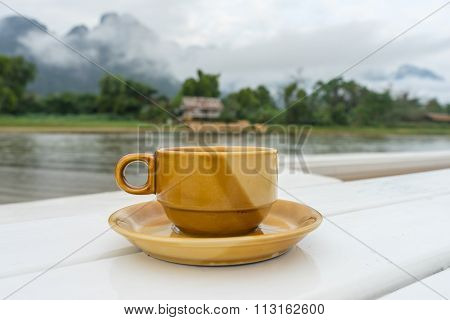 Coffee Cup Ceramic With Song River (vang Vieng Laos) And Cloud Background.