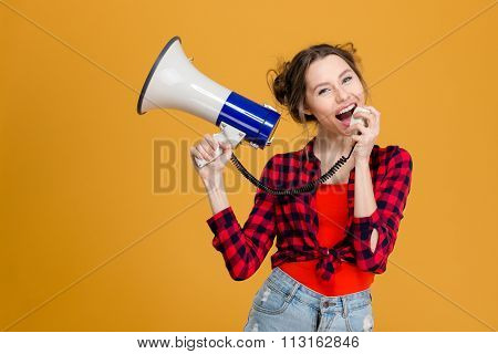 Portrait of a young casual woman screaming in megaphone over yellow background
