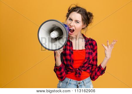 Angry mad young woman in plaid shirt screaming in megaphone over yellow background