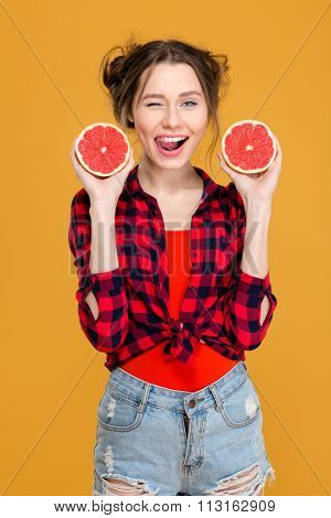 Flirty smiling young woman in checkered shirt and jeans shorts winking and posing with two halves of grapefruit over yellow background