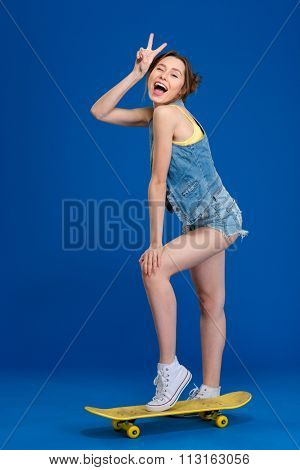 Cheerful happy young woman in jeans shorts and waistcoat standing on skateboard and showing victory sign over blue background