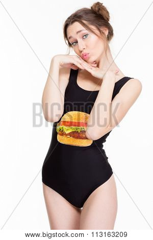 Pretty cute lovely young woman in black swimwear posing and making duck face isolated over white background