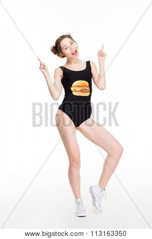 Joyful beautiful young female in black swimwear and white sneakers pointing up with both hands over white background