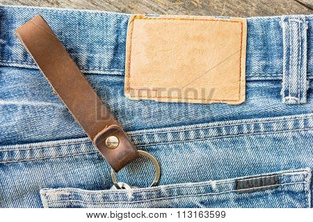 Blank Leather Jeans Label On A Blue Jeans, Wooden Background.