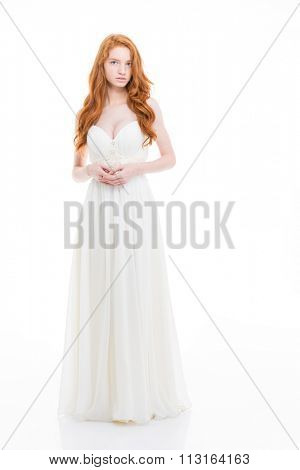 Full length of beautiful young woman with wavy long red hair in wedding dress standing over white background