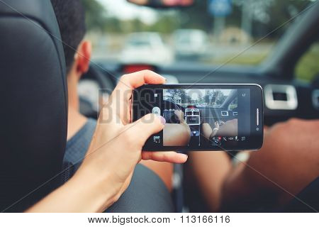 Female taking photo with mobile phone camera with vehicle during road trip