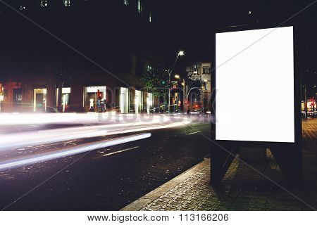 Public information board in night city with movement of cars on background