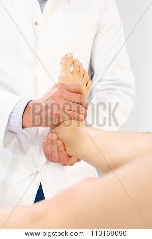 Orthopedic surgeon examines the patient's foot