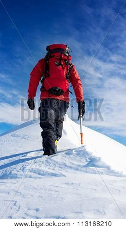 Mountaineer walks on the summit of a snowy peak. Concepts: determination, courage, effort, self-realization. Sunny winter day, european Alps.