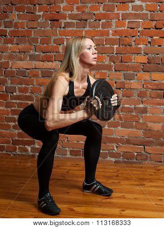 Attractive Athletic Woman In Black Leggins Performing Squatting