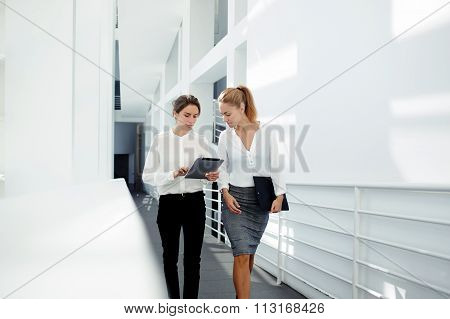 Two female managing directors discussing ideas of project on digital tablet while walking down