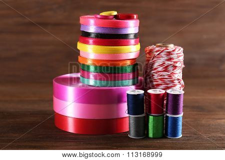 Spools of color ribbon and thread on wooden background