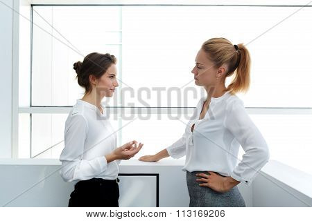Female worker explaining to her dissatisfied boss why she was late for work while standing in office