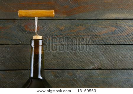 Bottle of wine with corkscrew on wooden background
