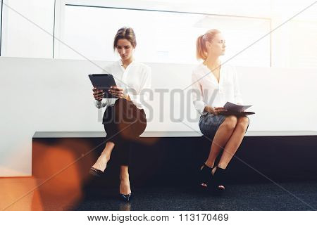 Businesswoman working on touch pad while offended colleague sitting near