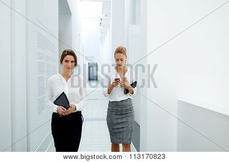 Two mobile phones businesswoman using telephone while her partner going near