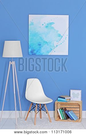 Room design with white floor lamp, chair, bookcase and picture over blue wall