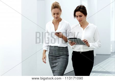 Two female professional staff using smart phone and touch pad while walking in modern office