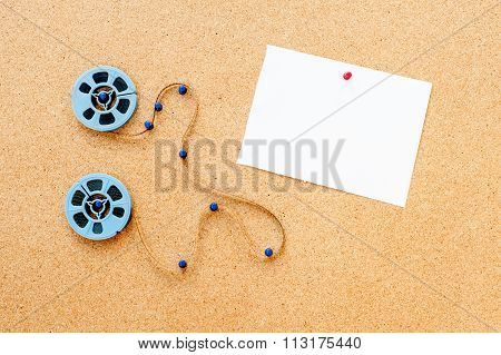 Two Little Movie Reel And White Card Pinned On Cork Board
