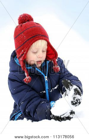 Young Child Playing In Winter Snow Making Snowball