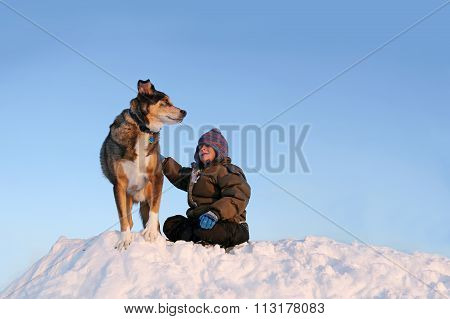 Young Child Playing Wtih Pet Dog Outside In Winter Snow