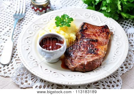 Medium rare grilled Beef steak with mashed potatoes and barbecue sauce