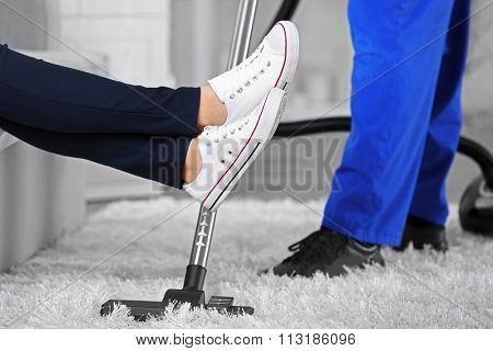 Cleaning concept - man cleaning the room with carpet sweeper, close up