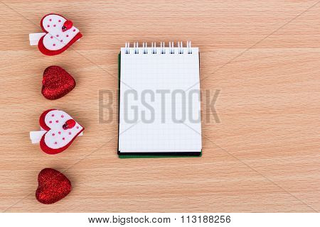 Four Hearts And A Notebook Lay On The Table