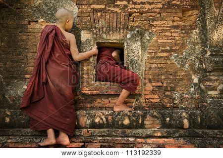 Two playful young novice monks climbing into Buddhist temple from window, Bagan, Myanmar.