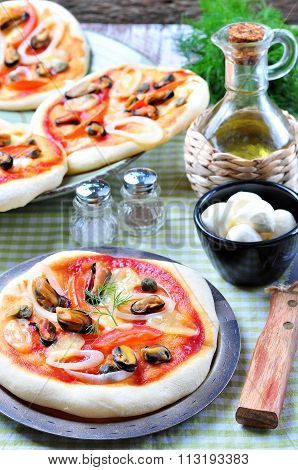 homemade mini pizza with mussels, calamari, onion, tomato, mozzarella and capers