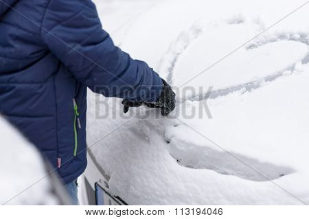 Person Drawing A Heart In The Snow On A Car
