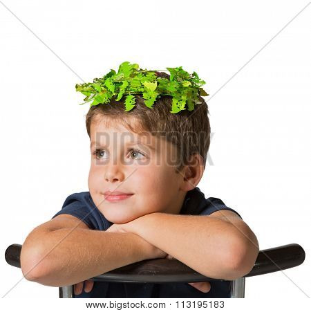 Very beautiful boy in a carnival wearing a crown of shiny green leaves. He sits astride a chair