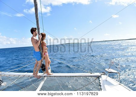 Couple standing in catamaran net looking at scenery