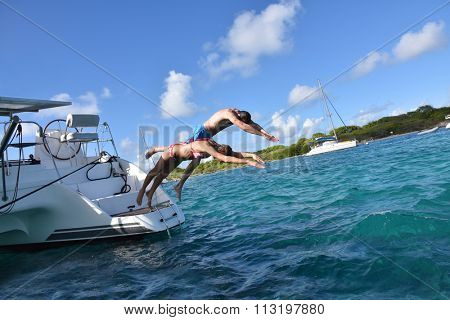 Couple diving from sailboat into Caribbean water