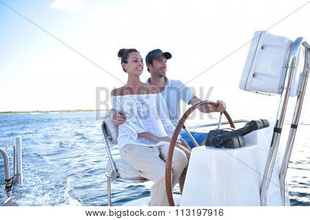 Couple on a sailboat sitting at wheel