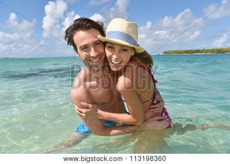 Cheerful couple in crystal caribbean sea