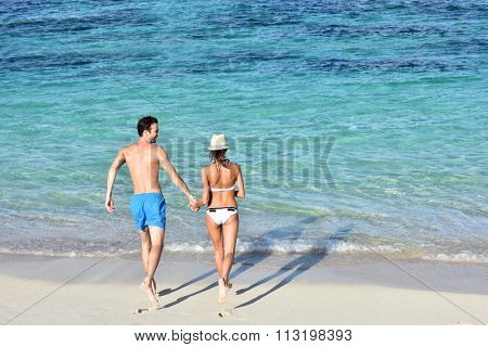 Back view of couple running into Caribbean water