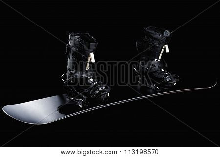 Black snowboard with black bindings and black boots isolated on black.